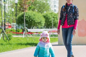 child walks with mom in sunglasses