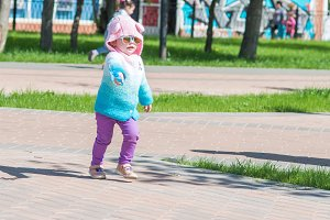 the child is walking in sunglasses