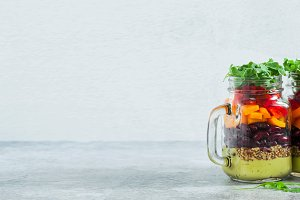 banner of rainbow colored salad in jars on the table. with beans