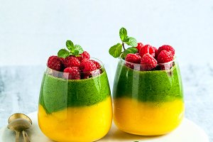 Fresh vegan layered dessert in a glass of colored smoothies of m