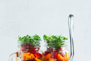 rainbow colored salad in jars on the table. with beans, fresh ve