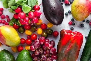 colorful fruits, vegetables and berries scattered on a table of
