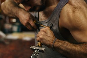 Blacksmith fastens leather winding