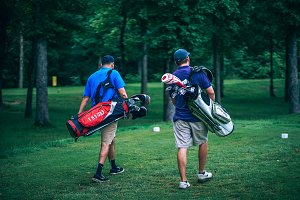 Golf Players Carrying Golf Bags