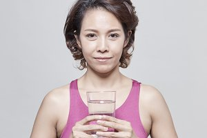 Beautiful Asian short hair woman in fitness suit standing holding a glass of water on gray background