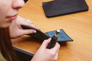Tanner polishes edges of leather