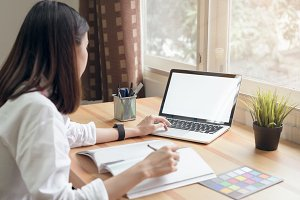 Businesswoman in office in casual shirt. Use computer for graphic designer and choose a color sample to match the publication.