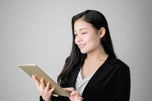 Smiling business women are holding tablet and using online applications. Gray background provides soft lighting.
