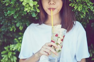 close up of beautiful woman relaxing eat drink fruit juice in the garden. Vacation time and summer.