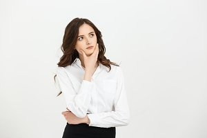 Business Concept: Thoughtful businesswoman with a finger under chin looking. Isolate on white background.