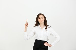 Business Concept: Attractive young Caucasian girl smiling and pointing her index finger to the top. She looks enthusiastic, isolated on white background