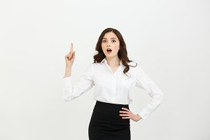 Business Concept: Attractive young Caucasian girl open her mouth and pointing her index finger to the top. She looks enthusiastic, isolated on white background
