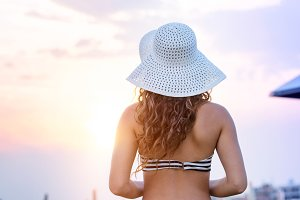 Woman on beach wearing bikini and hat, rear view