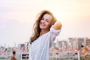 Beautiful woman on beach in white shirt, smiling, sunset