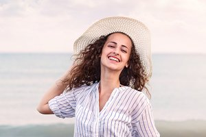 Woman on beach wearing shirt and hat, smiling, holding head
