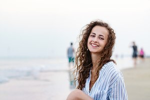 Beautiful woman sitting on beach in white shirt, smiling