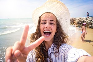 Beautiful woman on beach, laughing, taking selfie, sunny day