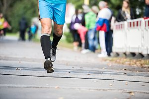 Legs of unrecognizable runner outdoors. Long distance running.