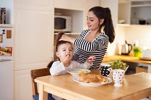 Little girl eating breakfast, mother doing her hair