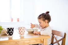 Little girl sitting at the table, eating breakfast by Jozef Polc in People
