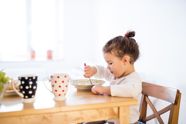 People Stock Photos: HalfPoint - Little girl sitting at the table, eating breakfast