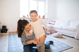 Mother dressing her daughter in the morning their living room