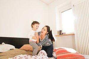 Mother having fun with her daughter in her bedroom