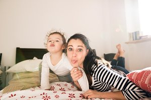 Mother having fun with her daughter in her bedroom