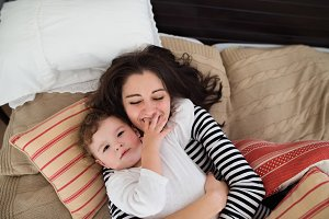 Mother with her daughter lying on bed, having fun