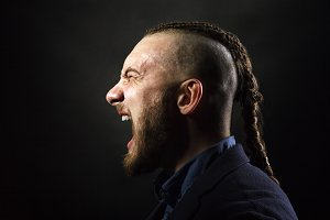 man with dreadlocks screams in a rage, looks like a viking, Iroquois haircut