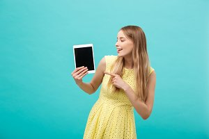 Happy attractive caucasian woman pointing finger on tablet at copy space isolated over blue background