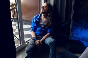 man with long hair and beard sits at home on a chair by the window