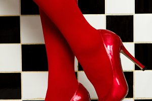female legs in red pantyhose and shoes on high heels on a background