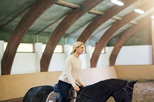 Female practicing trotting in indoor riding hall