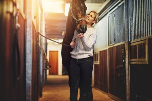 Young woman prepping her horse in stables before a ride