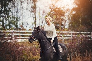 Young woman riding her horse through a pasture in autumn
