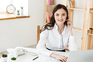 Young friendly operator woman agent or business woman with headsets working in a call centre.