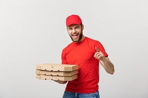 Delivery Concept: Handsome pizza delivery man courier in red uniform with cap holding pizza boxes. Isolated on white.