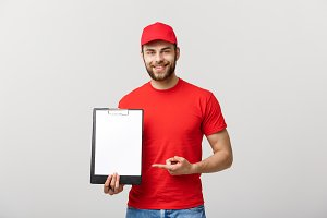 Delivery man in red uniform holding white empty blank paper isolated on white background. Copy space advertisement. Place for text or image