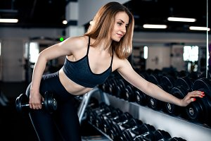 Girl doing triceps exercise with dumbbells