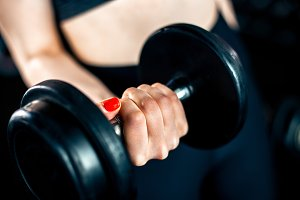 Girl doing bicep exercise with dumbbells
