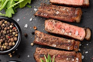 Closeup ready to eat steak new York beef breeds of black Angus with herbs, garlic and butter on a stone Board. The finished dish for dinner on a dark stone background. Top view