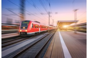 High speed red train with motion blur effect on the railway station