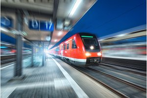 High speed train in motion on the railway station at night