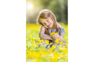 Happy little girl on blooming meadow