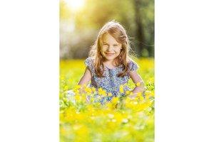 Happy little girl on blooming meadow