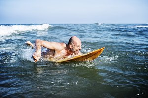 A senior man with a surfboard