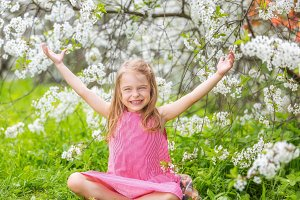 Happy little girl in cherry blossom garden
