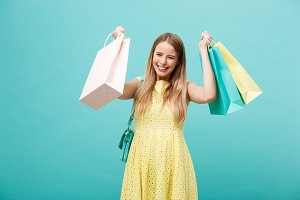 Portrait of young happy smiling woman with shopping bags. Blue Background.