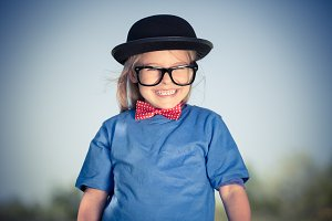 Funny happy little girl in bow tie and bowler hat.